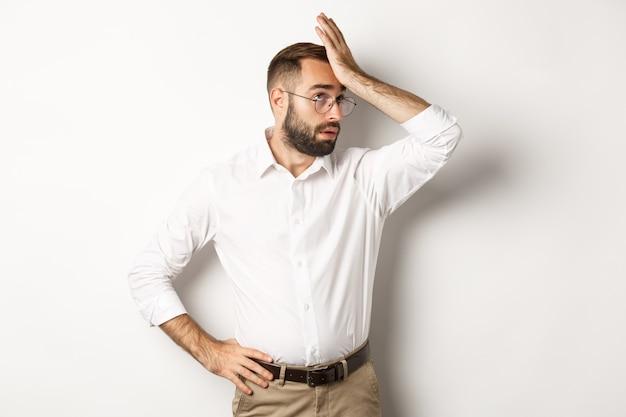 Gerente homem irritado revira os olhos e dá um tapa na testa, palma da mão de algo cansativo Foto gratuita