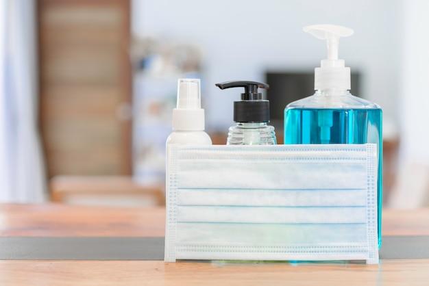 Germe de coronavírus protetor com máscaras e álcool gel ou spray de desinfetante para as mãos para lavar as mãos para proteger o vírus corona na mesa de madeira Foto Premium