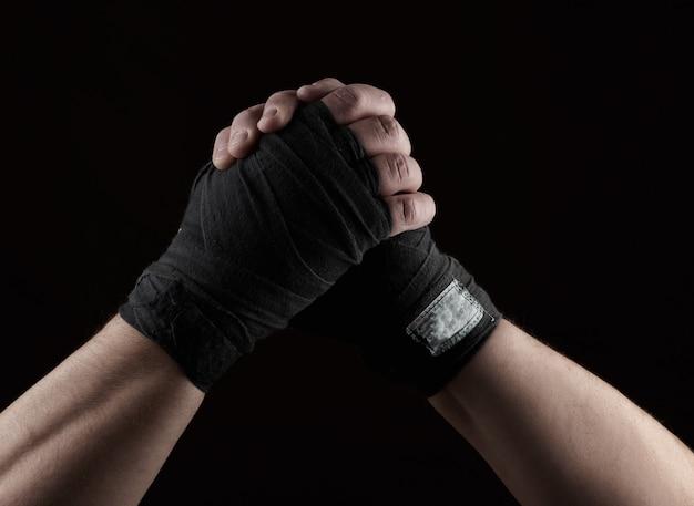 Gesto de amizade, duas mãos masculinas de um atleta amarrado com um curativo têxtil preto Foto Premium