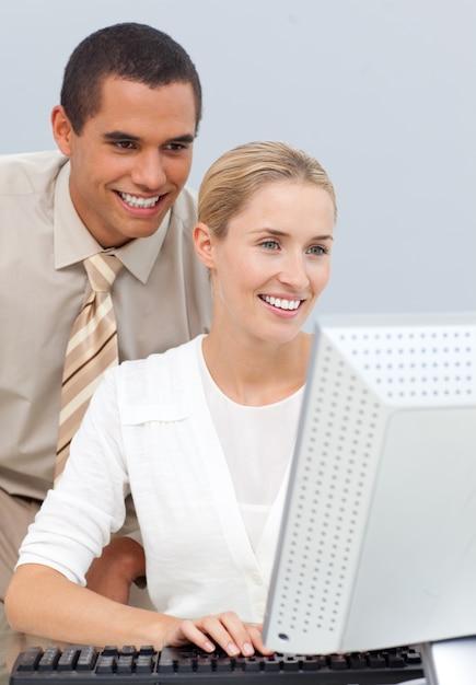 Gestor alegre ajudando uma empresária com o computador Foto Premium