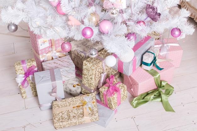Giftboxes, bolas de decorações de natal-de-rosa e branco pendurado em uma árvore de natal branca decorativa Foto Premium