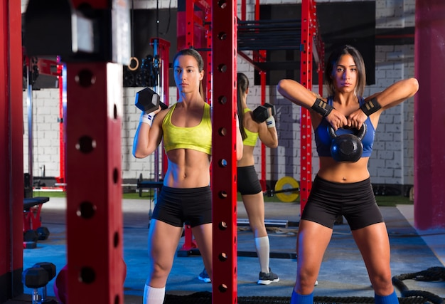 Ginásio mulheres com treino de barra e kettlebell Foto Premium
