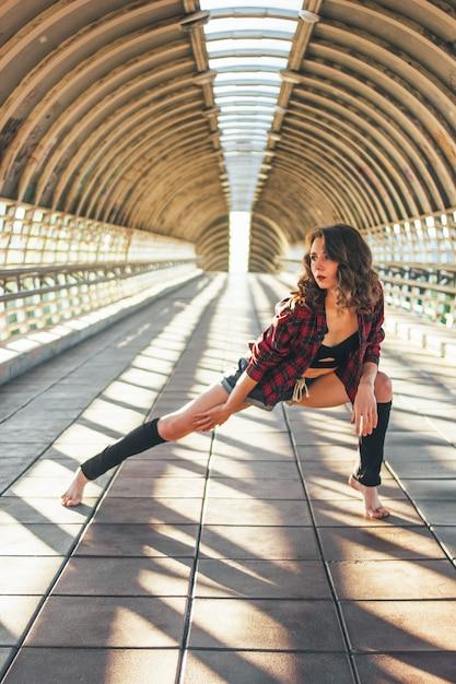 Ginasta de dançarina de rua jovem morena esbelta senta-se em pose de divisões na ponte de rua Foto Premium