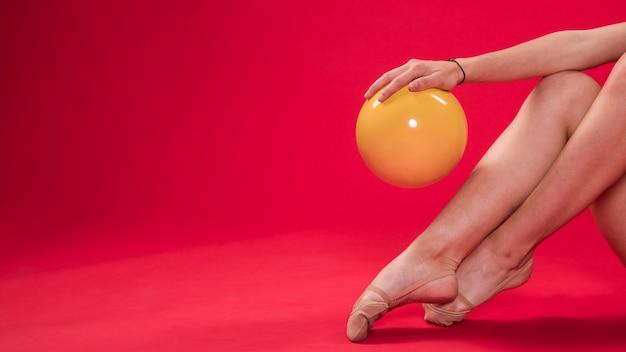 Ginasta fazendo posições com a bola Foto gratuita