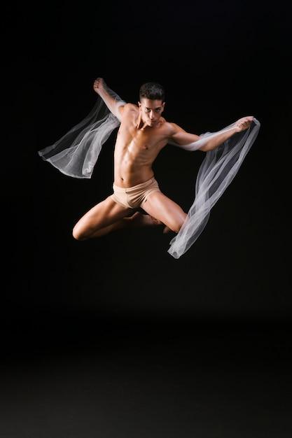 Ginasta masculino que salta no ar Foto gratuita