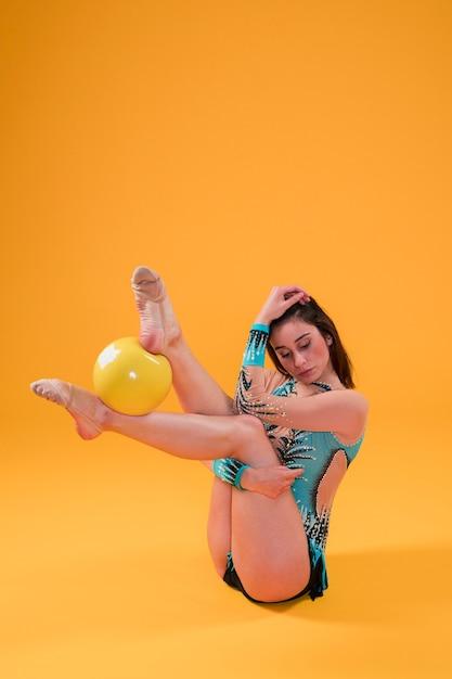 Ginasta rítmica usando a bola Foto gratuita
