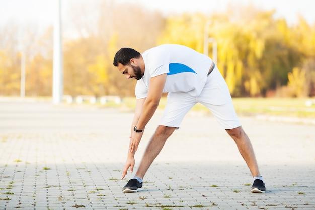 Ginástica. homem de alongamento fazendo exercícios de alongamento. estendendo-se para a frente, estique as pernas Foto Premium