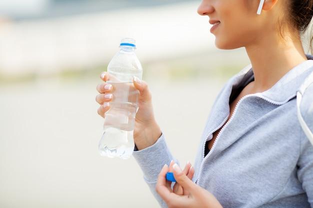 Ginástica. mulher bonita, beber água e ouvir música depois de correr Foto Premium