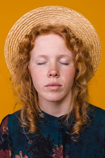 Ginger sardenta mulher de chapéu com os olhos fechados Foto gratuita