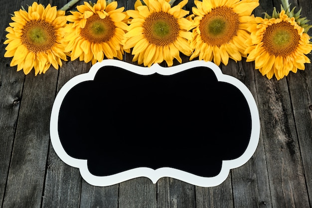 Girassóis amarelos e etiqueta preta em um fundo de madeira Foto Premium