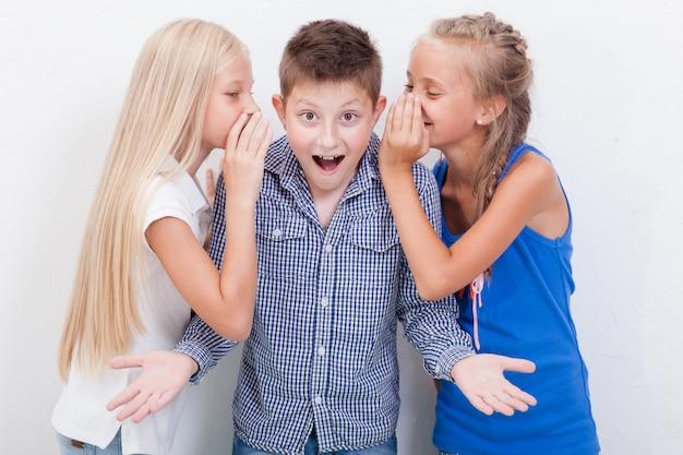 Girsl adolescente sussurrando nos ouvidos de um menino adolescente secreto no fundo branco Foto gratuita