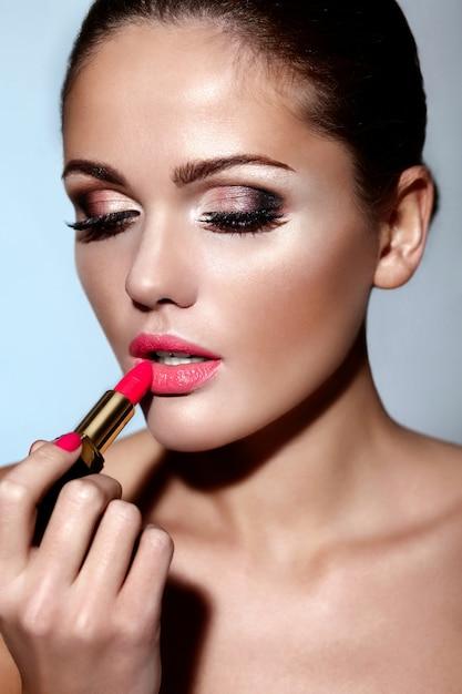 Glamour closeup retrato do modelo caucasiano morena jovem bonita aplicando maquiagem batom nos lábios com pele limpa perfeita Foto gratuita