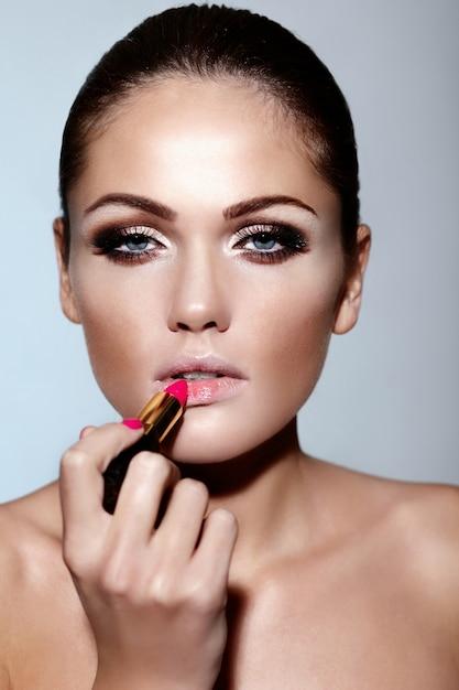 Glamour closeup retrato do modelo sexy caucasiano morena jovem bonita aplicar maquiagem batom nos lábios com pele limpa perfeita Foto gratuita