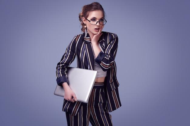 Glamour elegante mulher de moda terno e óculos com notebook Foto Premium