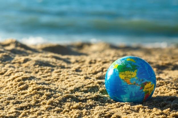 Globo da terra do planeta em uma praia arenosa em um fundo do oceano. Foto Premium