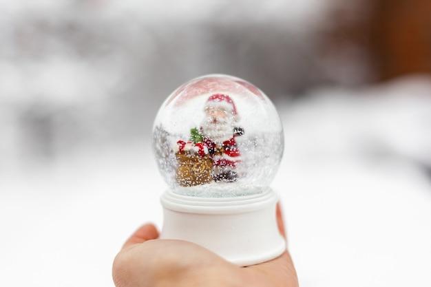 Globo de neve de natal na mão Foto Premium