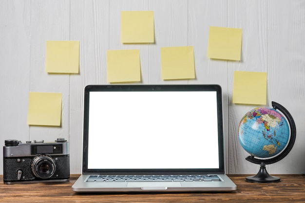 Globo e câmera perto de notas e laptop Foto gratuita
