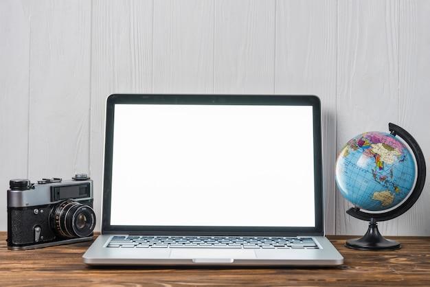 Globo e câmera perto do laptop Foto gratuita