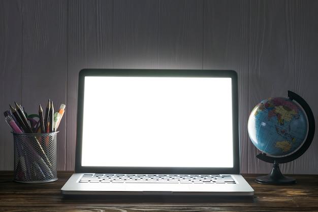 Globo e papelaria perto do laptop Foto gratuita