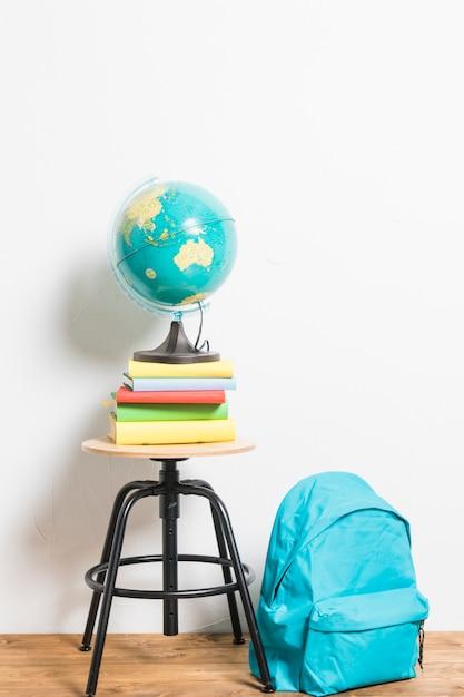 Globo em livros colocados na cadeira de fezes ao lado de mochila Foto gratuita
