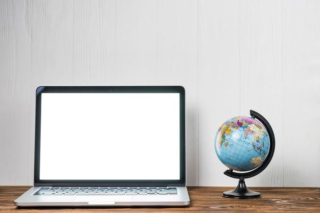 Globo perto do laptop Foto gratuita