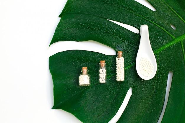 Glóbulo homeopáticos em três garrafas de vidro no fundo em folha de palmeira molhado. Foto Premium