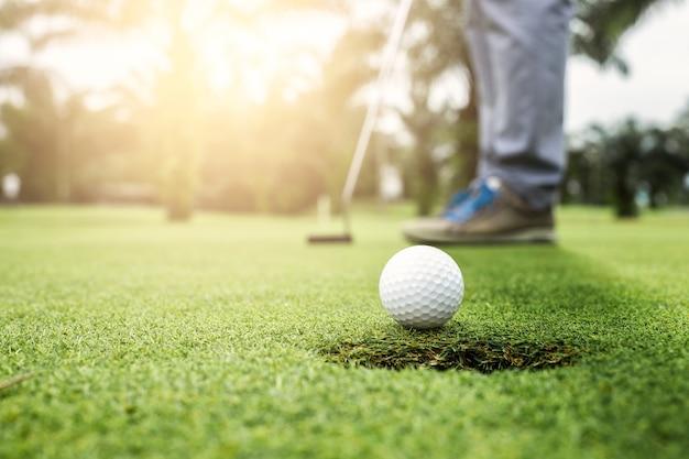 Golfista colocando a abordagem de bola de golfe para o buraco de golfe no golfe verde Foto Premium