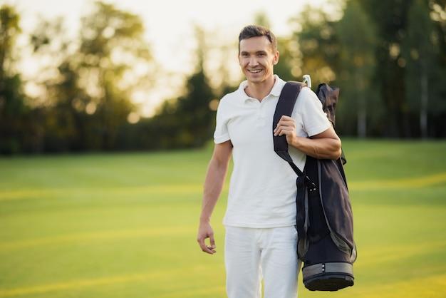 Golfista com saco de clubes deixa um curso do golfo. Foto Premium