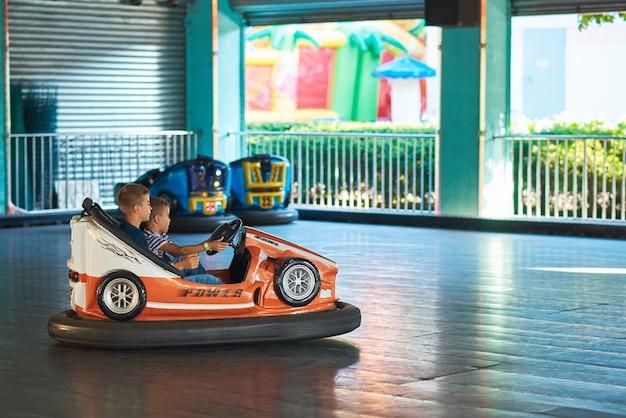 Gomel, bielorrússia - 22 de agosto de 2019: dois garoto se divertir em um carrinho de choque no parque de diversões Foto Premium