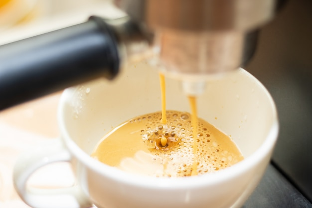 Gota de café fresco cair perto da máquina de café Foto Premium