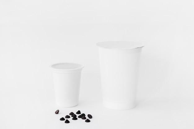 Gotas de chocolate perto de copos de leite Foto gratuita