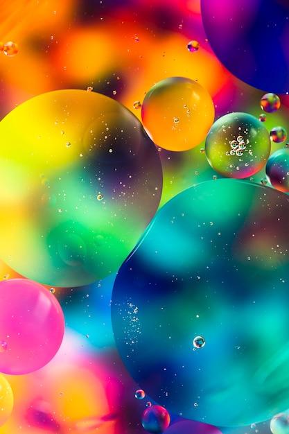 Gotas de óleo de arco-íris sobre um fundo abstrato de superfície de água Foto gratuita