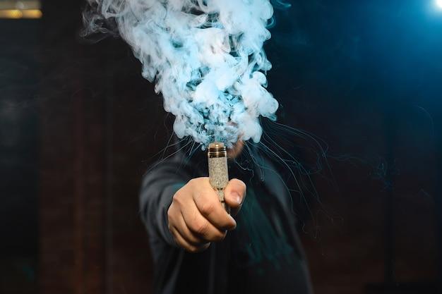 Gotejador em uma mão, fazendo uma nuvem de fumaça Foto gratuita