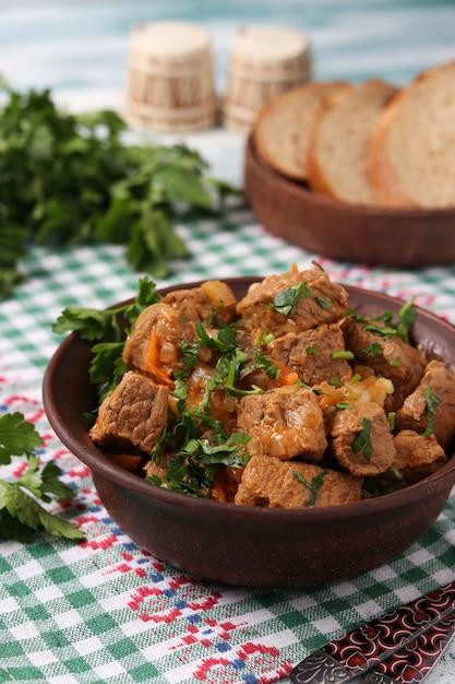 Goulash de carne está localizado em uma tigela marrom em cima da mesa Foto Premium
