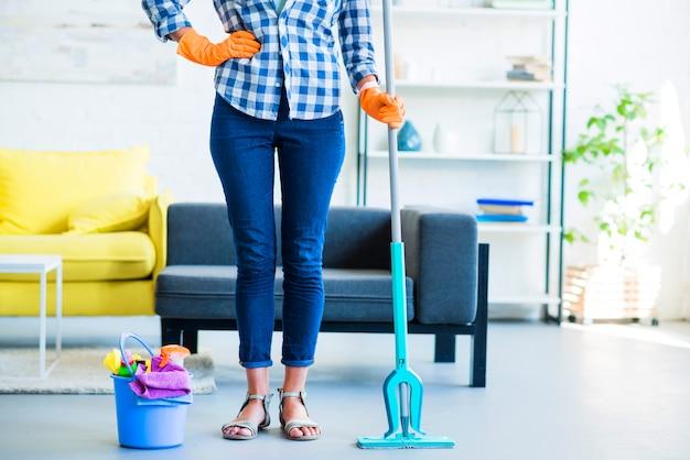 Governanta feminina com equipamentos de limpeza em casa Foto gratuita