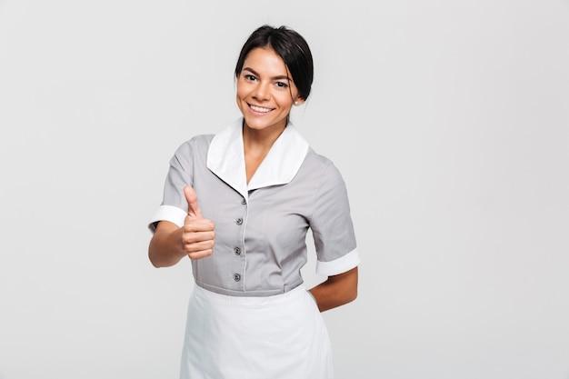 Governanta morena alegre em uniforme mostrando o polegar para cima gesto Foto gratuita