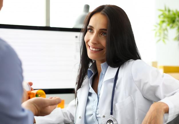 Gp caucasiano bonito que fala com o visitante masculino que dá a ele o retrato da prescrição Foto Premium