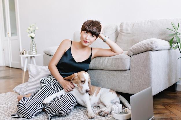 Graciosa garota de cabelos castanhos em um top preto relaxando no carpete perto de almofadas listradas e acariciando o filhote de cachorro beagle Foto gratuita