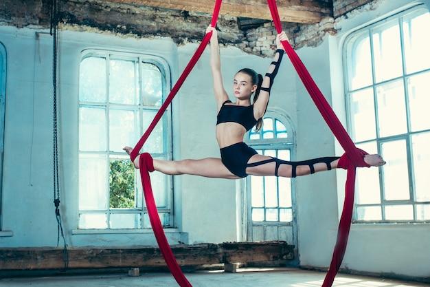 Graciosa ginasta fazendo exercícios aéreos com tecidos vermelhos Foto gratuita