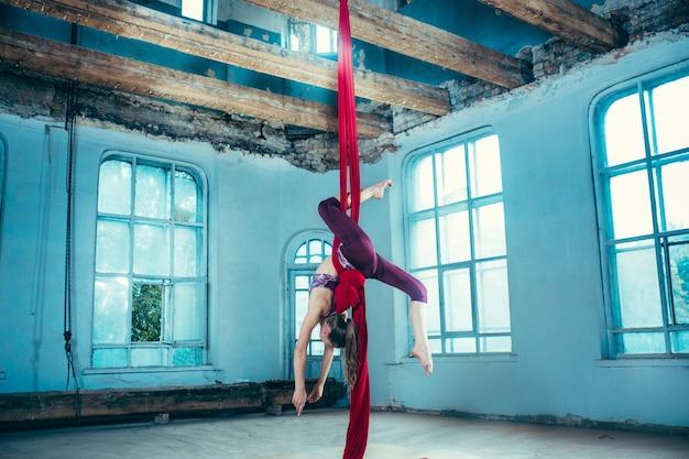Graciosa ginasta realizando exercícios aéreos com tecidos vermelhos sobre fundo azul antigo loft. garota apta jovem adolescente caucasiana. o circo, acrobático, acrobata, artista, esporte, fitness, conceito de ginástica Foto gratuita