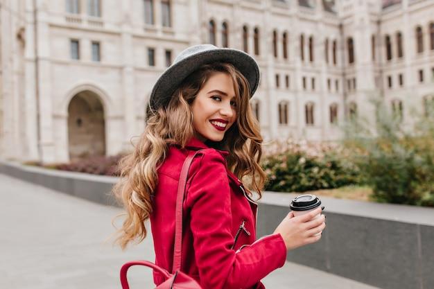 Graciosa mulher branca com chapéu cinza olhando por cima do ombro enquanto explora a parte antiga da cidade Foto gratuita