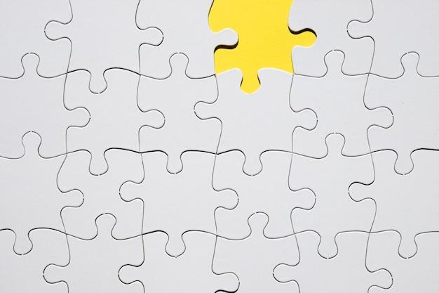 Grade de quebra-cabeça branca com falta de peça de quebra-cabeça Foto gratuita