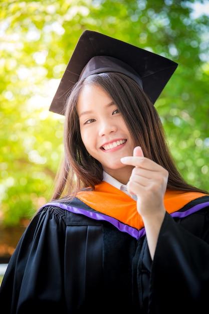 Graduação bonito asiática do retrato das mulheres com fundo verde da natureza, universidade de tailândia. Foto Premium