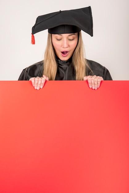 Graduação surpresa segurando um mock-up cartaz vermelho Foto gratuita