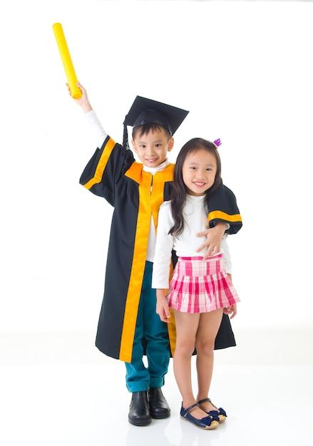 Graduado asiático da criança da escola no vestido e no tampão da graduação. tirando foto com a irmã e o irmão. Foto Premium