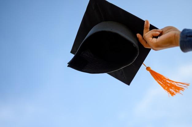 Graduados segurar um chapéu preto com uma borla amarela ligada ao céu. Foto Premium