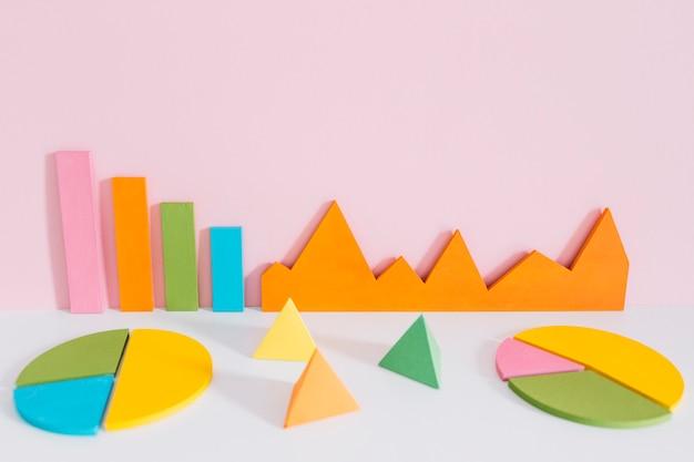 Gráfico colorido diferente com formas de pirâmide contra fundo rosa Foto gratuita