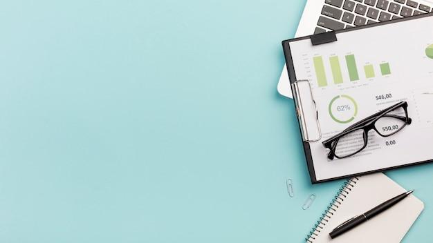 Gráfico de orçamento de negócios e óculos no laptop com o bloco de notas em espiral e caneta contra o fundo azul Foto gratuita