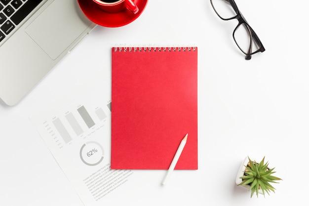 Gráfico de orçamento, o bloco de notas em espiral, lápis, planta do cacto, laptop e óculos no fundo branco Foto gratuita