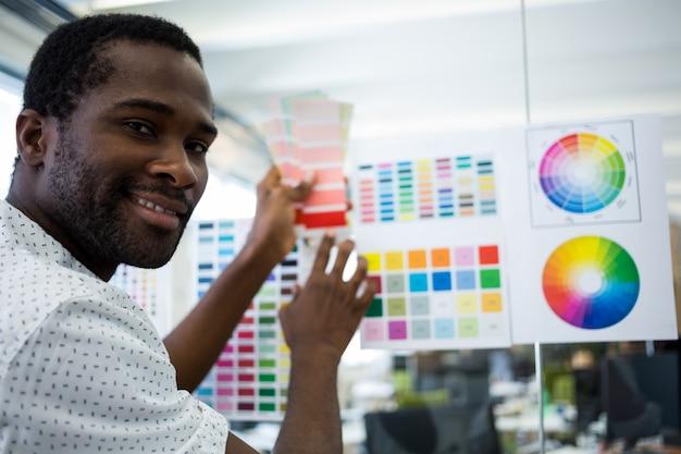 Gráfico holding designer de amostra de cor masculino Foto gratuita